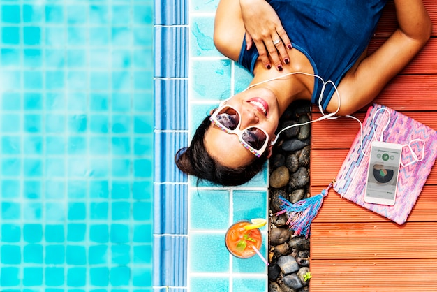 Closeup of asian woman listening to music by the pool