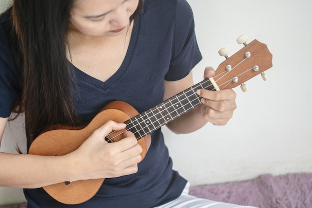 Closeup asian woman playing ukulele on white cement wall texture with copy space