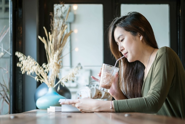 Closeup asian woman reading a book and drinking iced chocolate at the wooden counter desk in coffee shop