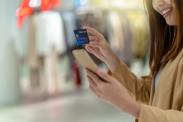 Closeup asian woman using credit card with mobile for online shopping in department store