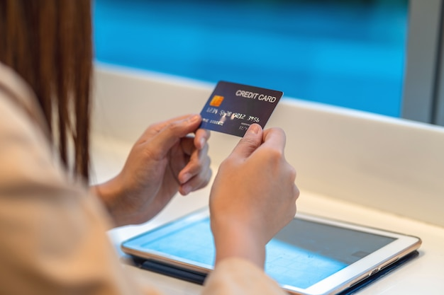 Женщина крупного плана азиатская используя кредитную карточку с таблеткой для онлайн покупок в универмаге над стеной магазина одежды, бумажником денег технологии и концепцией онлайн оплаты, модель-макетом кредитной карточки