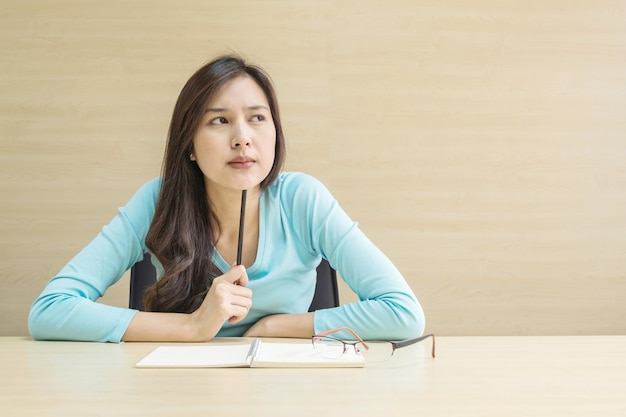 Closeup asian woman working with thinking face emotion and a pencil in her hand