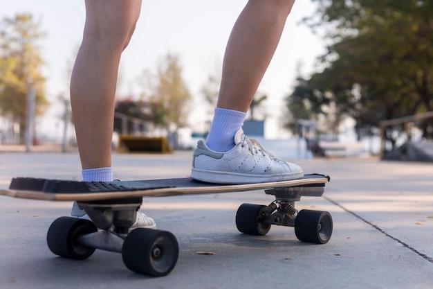クローズアップアジアの女性は美しい朝に屋外でスケートやスケートボードをサーフィンします