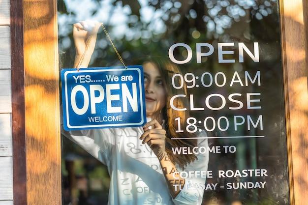 Азиатская молодая азиатская женщина крупного плана устанавливает открытый знак в стеклах магазина для приветствия