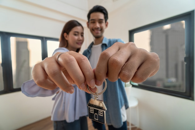 Closeup asian young lover hand holding the home key chain together