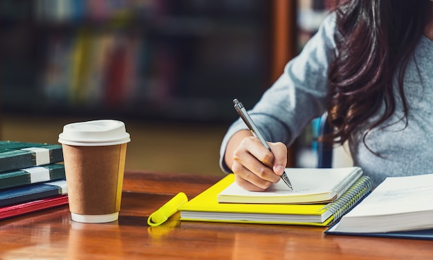 Closeup asian young student hand writing homework in library of university or colleague
