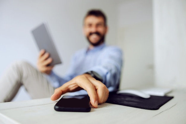 Closeup of attractive businessman dressed business casual sitting at office and reaching for smart phone. selective focus on hand.