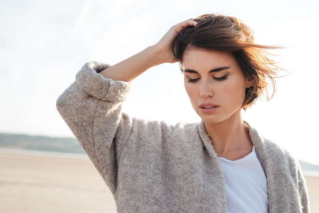 Closeup of attractive pensive young woman in coat on the beach in autumn