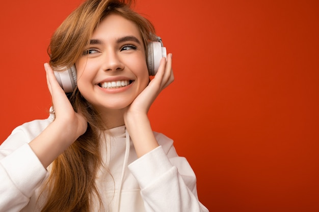 クローズアップ魅力的なポジティブな若いブロンドの女性は、白いパーカーを身に着けている白いワイヤレスブルートゥースヘッドフォンを身に着けているカラフルな壁の上に分離された良い音楽を横に見て聞いています。