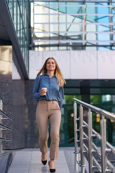 ビジネスビルのテイクアウトコーヒーと動いているクローズアップの魅力的な女性。屋外の温かい飲み物と紙コップを保持している肖像画のブロンドの女の子。