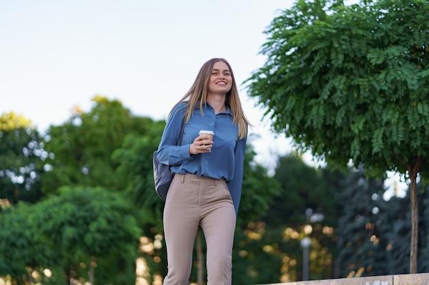 街でテイクアウトのコーヒーと動きのある魅力的な女性をクローズアップ。屋外の温かい飲み物と紙コップを保持している肖像画のブロンドの女の子。
