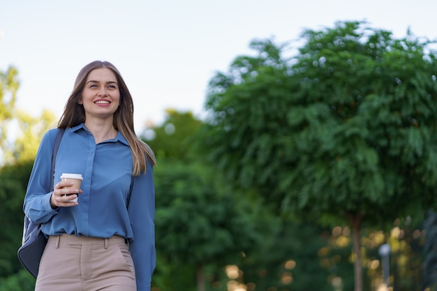 Closeup attractive woman in motion with takeaway coffee on city street. portrait blonde girl holding paper cup with hot drink outdoor.
