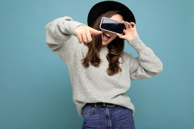 Closeup of attractive young funny happy woman wearing black hat and grey sweater holding phone pointing finger finger at camera isolated on background.