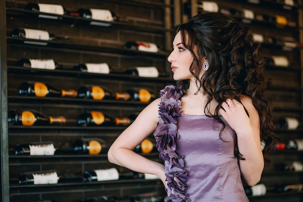 Closeup of attractive young woman standing in front of wine and champagne bottles