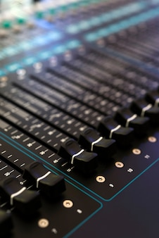 Closeup of audio mixing console, shallow depth of field