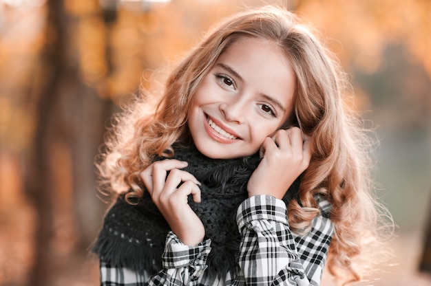 Closeup autumn portrait of teenage girl  smiling over yellow leaves