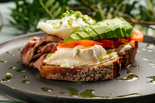 Closeup on avocado sandwich with roast beef and poached egg for breakfast