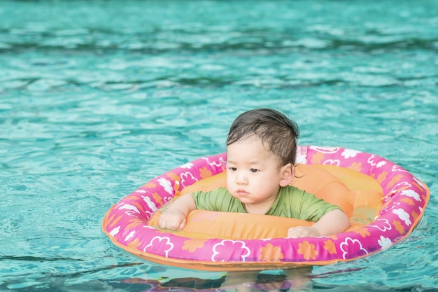 Closeup a baby boy sit in a boat for children in the swimming pool background