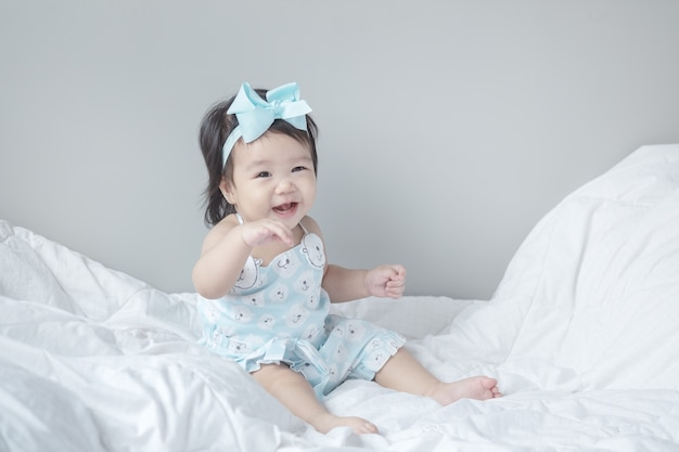 Closeup baby girl sit on bed in funny motion Premium Photo