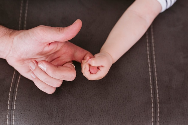 Closeup of a baby holding father's finger at home. family and love concept