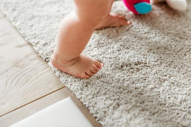 Primo piano delle gambe del bambino mentre levandosi in piedi