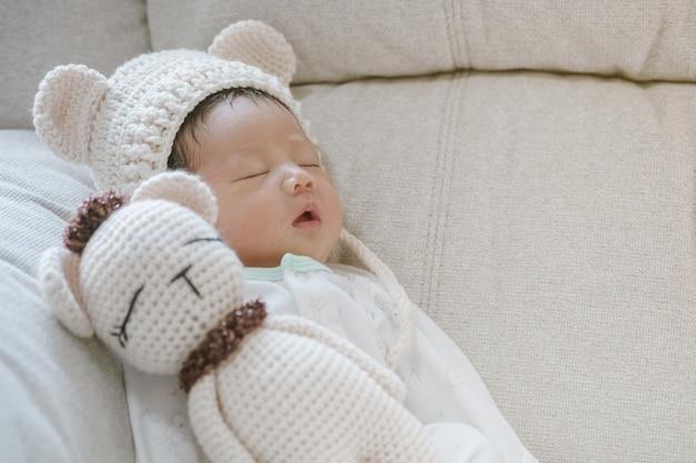 Closeup a baby sleeping comfortably on sofa with bear doll