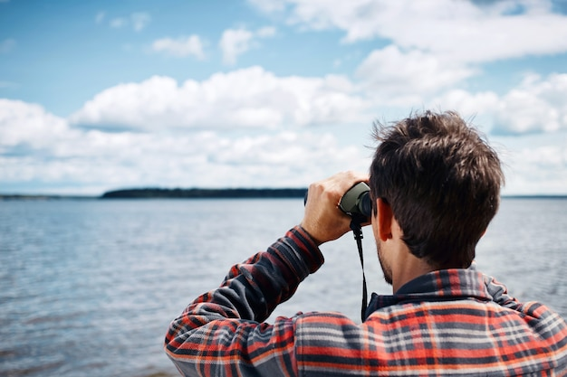 双眼鏡を通して見ている男のクローズアップの後ろの肖像画