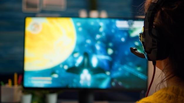 チャンピオンシップでチームメイトとヘッドセットに話しかけるコンピュータービデオゲームをプレイするプロゲーマーの女性の肖像画のクローズアップバックアップ。コンピューターで遊ぶプロゲーマーの多様なeスポーツチーム