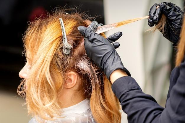 Крупным планом вид сзади рук парикмахера в перчатках, наносящих краску на прядь волос рыжей молодой женщины в парикмахерской