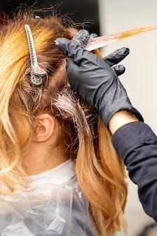 Крупным планом вид сзади руки парикмахера в перчатках, наносящих краску на прядь волос рыжей молодой женщины в парикмахерской