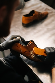 Closeup back view of unrecognizable shoemaker cleaning with brush old light brown leather shoes