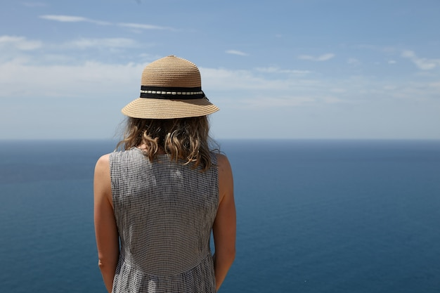 Closeup back view of unrecognizable slender blonde woman in dress and straw hat enjoying amazing seascape at viewpoint. romantic female admiring picturesque scenery over vast calm ocean and blue sky
