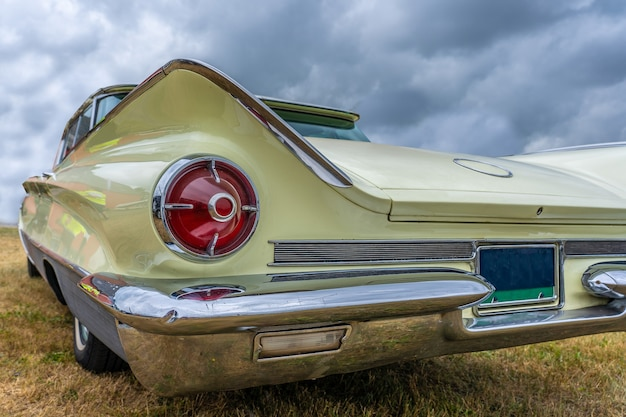 Closeup of the back of a vintage car in a field under a cloudy sky