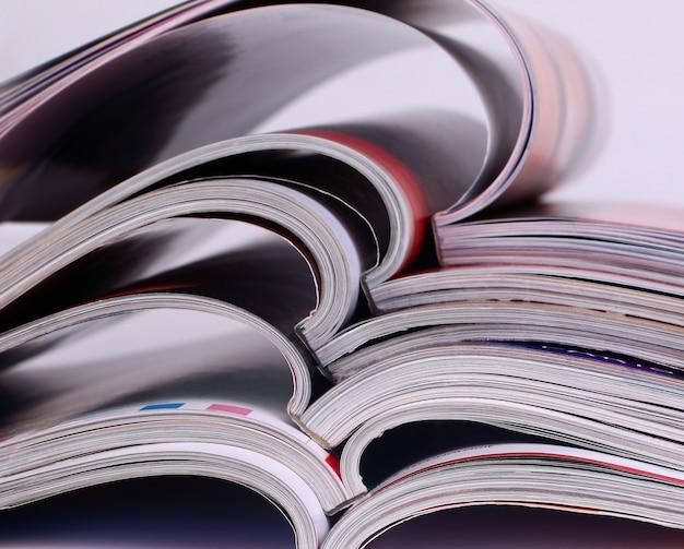 曲がりくねったページを持つ古い雑誌の山のクローズアップの背景