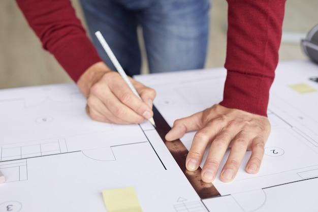 직장에서 책상에 기대어 청사진을 그리는 인식 할 수없는 건축가의 근접 촬영 배경,