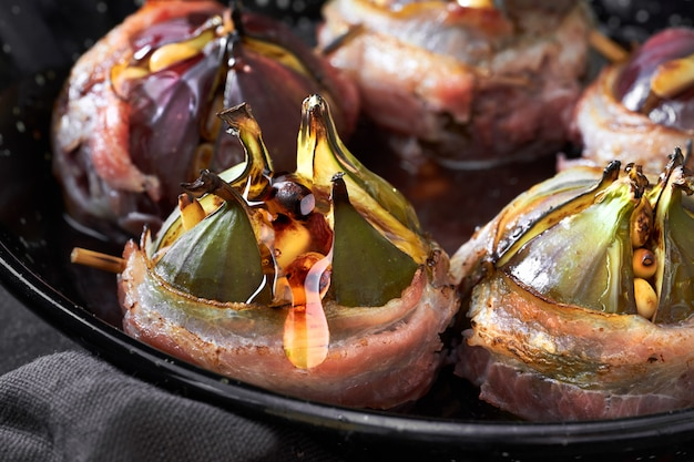 Closeup on baked fig wrapped in bacon, stuffed with pine nuts