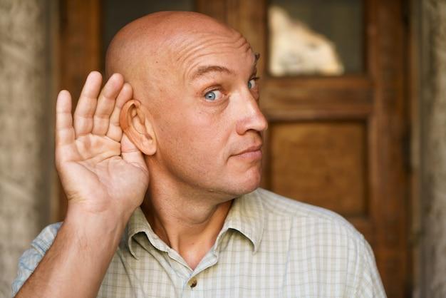 근접 촬영 대머리 남자는 빛 속에서 감정적인 백인 남자를 엿듣는 척 그의 귀에 손을 잡고...