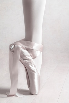 Closeup of ballerina leg in point with untied ribbons