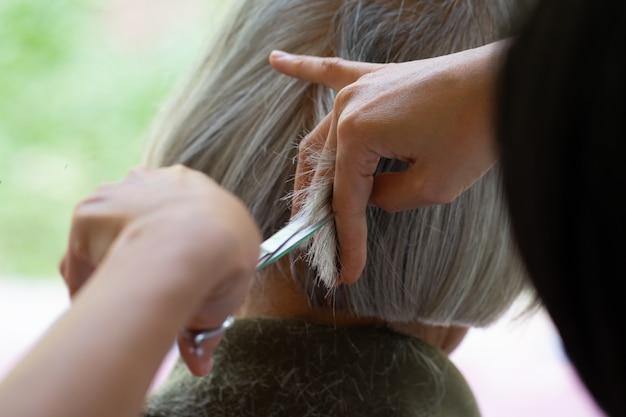 Closeup barber with scissors cutting hair