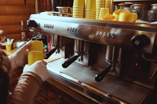 Closeup of barista's hands in gloves holding yellow takeaway paper cups and standing near a professional coffee machine