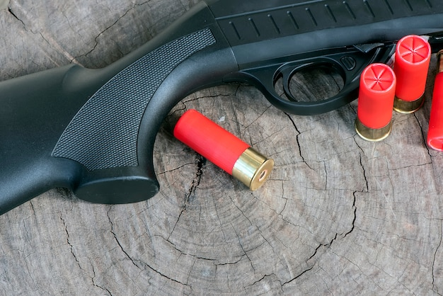 Closeup barrel shotgun and cartridges on wooden background.