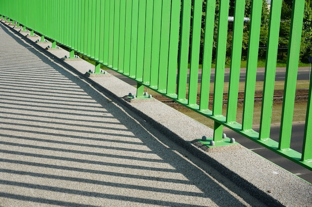 Closeup of the base of the green barrier of an overpass bridge