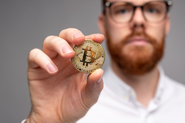Крупным планом бородатый парень в очках, вкладывающий деньги в биткойн, показывая золотую монету на сером фоне