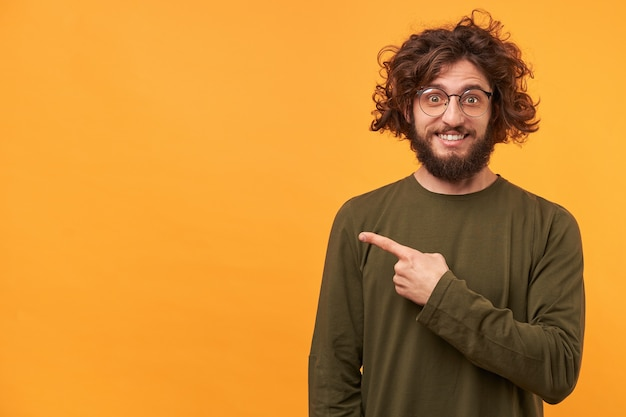 Closeup of a bearded young guy looks delighted gladden amazed pointing with index finger aside