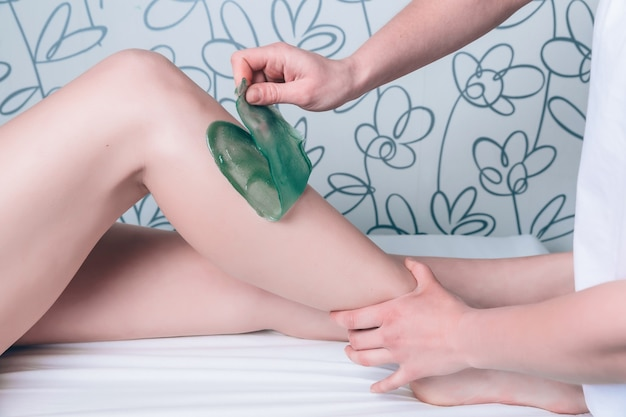 Closeup of beautician hands doing depilation to beautiful woman legs with hot wax in a beauty salon