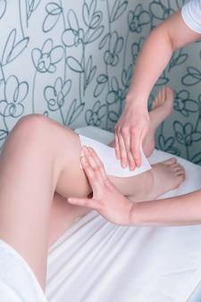 Closeup of beautician hands doing depilation to beautiful woman legs with wax strip in a beauty salon