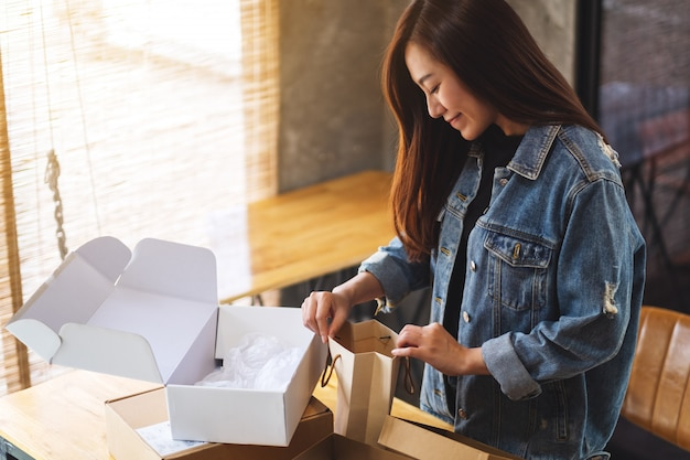 Closeup  of a beautiful asian woman opening and looking inside shopping bag at home for delivery and online shopping concept