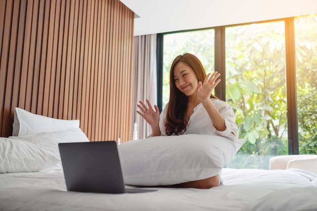 Closeup  of a beautiful asian woman waving hands while using laptop for video call while sitting on a bed at home