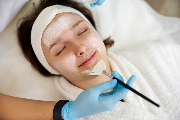 Closeup of beautiful brunette woman enjoying applying cosmetic facial mask with closed eyes. beauty treatment. skincare.