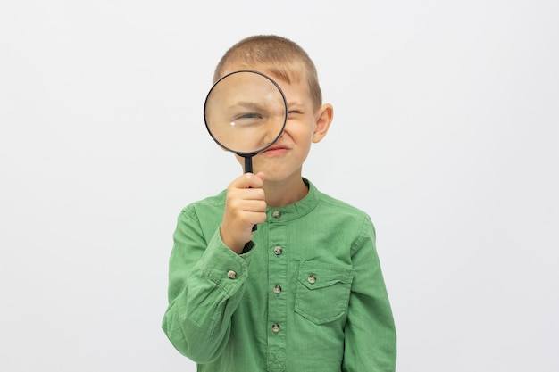 Closeup of a beautiful child looking through a magnifying glass loop over white